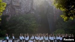 中国江苏淮安市钵池山公园的巨型老子雕像前,人们在国际瑜伽日练习瑜伽(2018年6月21日)。
