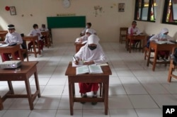 Siswa yang mengenakan masker duduk terpisah saat uji coba kelas dengan protokol COVID-19 di sebuah sekolah dasar di Jakarta, Jumat, 4 Juni 2021. (Foto: AP)