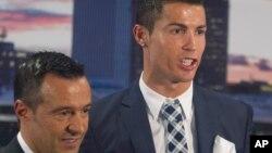 L'attaquant du Real Madrid, Cristiano Ronaldo, pose avec son agent Jorge Mendes après avoir reçu un trophée de bottine d'argent pour avoir marqué le plus de buts pour le club lors d'une cérémonie au stade Santiago Bernabeu à Madrid, en Espagne, 2 octobre 2015.