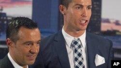 L'attaquant du Real Madrid, Cristiano Ronaldo, pose avec son agent Jorge Mendes après avoir reçu un trophée de bottine d'argent pour avoir marqué le plus de buts pour le club lors d'une cérémonie au stade Santiago Bernabeu à Madrid, en Espagne, 2 octobre