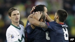 Slovenia's Milivoje Novakovic, left, reacts as United States' Landon Donovan, top center, celebrates with United States' Oguchi Onyewu, second from right, and United States' Clint Dempsey, right, after scoring during the World Cup group C soccer match bet