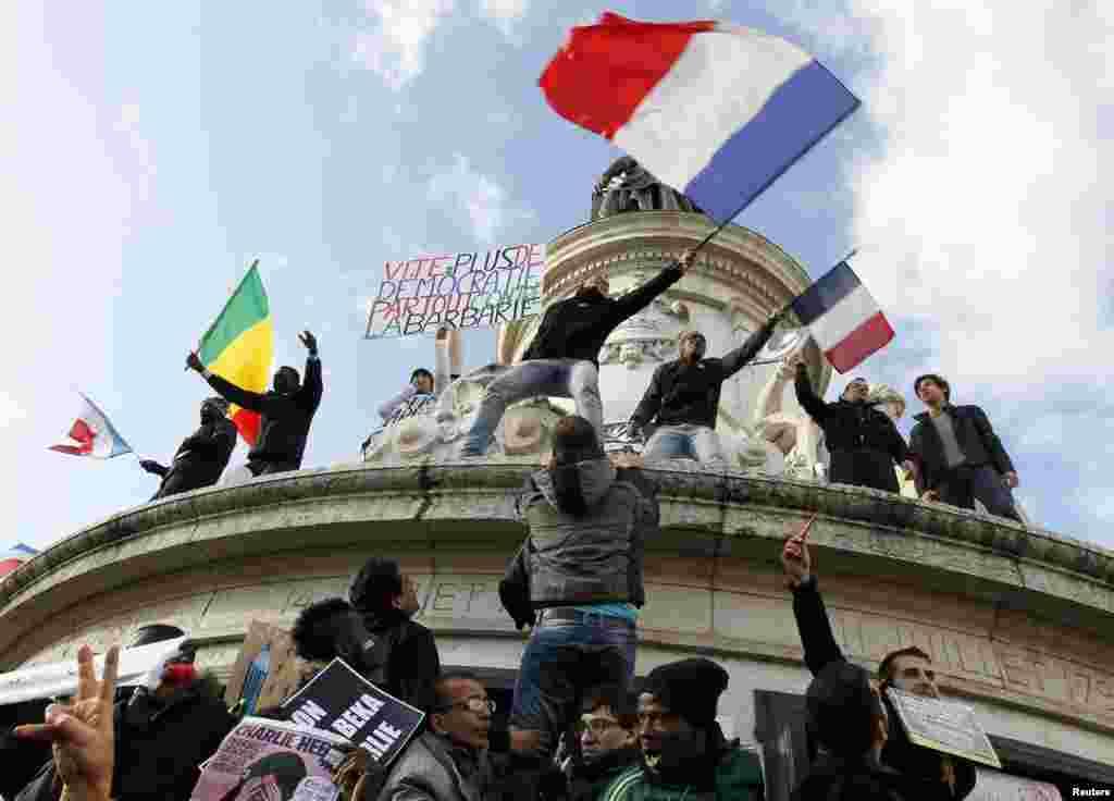 """Những người tuần hành cầm biểu ngữ """"Dân chủ nhanh hơn ở khắp mọi nơi chống lại sự man rợ"""" trong cuộc diễu hành đoàn kết trên các đường phố của Paris, Pháp, ngày 11/1/2015."""
