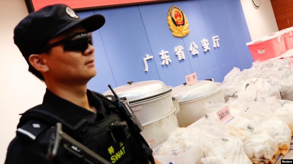 Một cảnh sát canh gác bên cạnh lô hàng ma túy bị thu giữ ở Trung Quốc năm 2018. Bộ Công an Việt Nam đã phát hiện và đang điều tra đường dây sản xuất ma túy của người Trung Quốc ở Việt Nam, trong đó 4 người Trung Quốc bị phạt