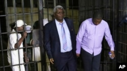 Zimbabwe's former finance minister, Ignatius Chombo, center, and Kudzanai Chipanga are led to a prison truck in Harare, Zimbabwe, Nov. 25, 2017. Chombo testified that armed men in masks and uniforms abducted him from his home during the military operation leading to the ouster of longtime leader Robert Mugabe and held him for a week in an unidentified location.