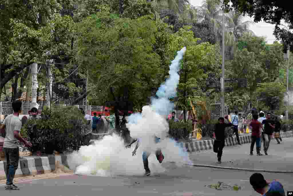 A student throws back an exploded tear gas shell at policemen during a protest for removing or reforming a quota system in government jobs in Dhaka, Bangladesh.