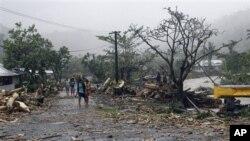 Warga setempat berjalan melewati jalanan yang porak poranda dipenuhi sampah dan serpihan pasca hantaman topan Evan di ibukota Samoa, Apia (14/12). Warga Fiji bersiap menghadapi topan Evan yang diperkirakan akan melanda wilayahnya, Minggu (16/12).