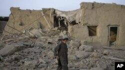 图为一名儿童7月14日经过一处当天造成被炸毁的房屋