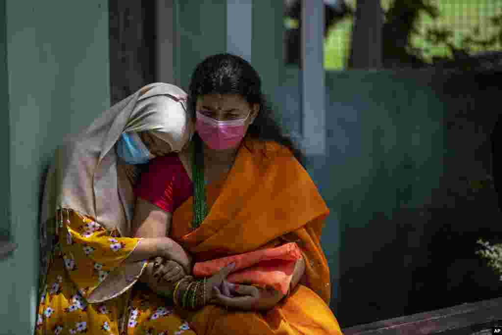 A physically disabled Nepalese girl waits with her mother to receive a dose of Johnson and Johnson vaccine at the Nepal Disabled Association Khagendra New Life Center in Kathmandu.