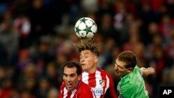 José Maria Gimenez d'Atletico, au centre, saute avec son coéquipier Diego Godin, à gauche, et le Daniel Schwaab du PSV, en lutte pour le ballon, lors d'un match de football du Groupe D entre l'Atlético de Madrid et le PSV Eindhoven au stade Vicente Calder