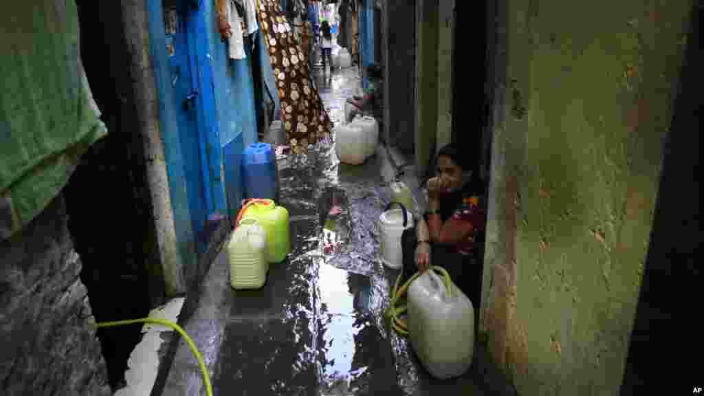 Des femmes récupèrent de l'eau d'un robinet dans un bidonville à Mumbai, en Inde, le 22 mars 2017.
