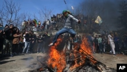 A masked supporter of imprisoned Kurdish rebel leader Abdullah Ocalan jumps over a Nowruz fire during the Nowruz celebrations in Istanbul, Turkey, March 22, 2015.