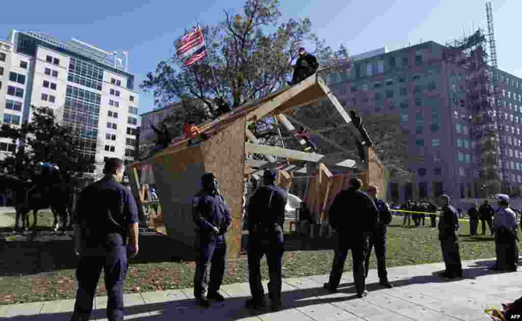 U.S. Park Police guard a structure set up by protesters overnight on McPherson Square, Sunday, Dec. 4, 2011 in Washington. Occupy DC protesters who are refusing to dismantle the unfinished wooden structure erected in the park. (AP Photo/Manuel Balce Ce