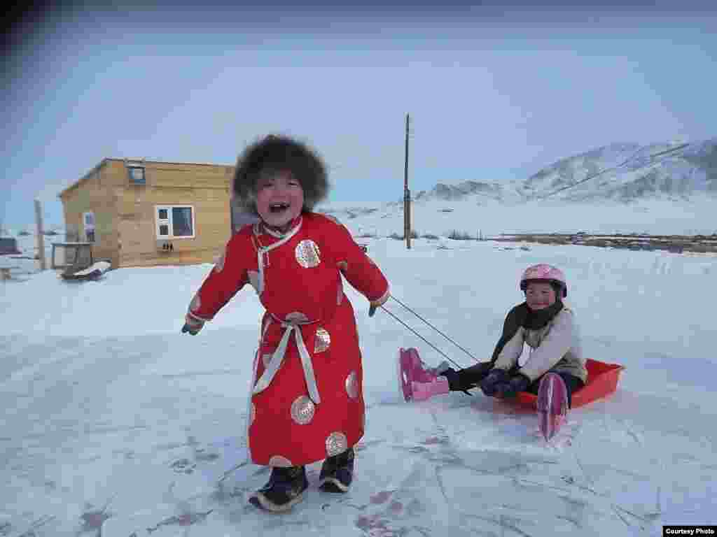 Little girls from a Mongolian herder family play on ice. (Photo submitted by Iderjargal to VOA Photo Contest)