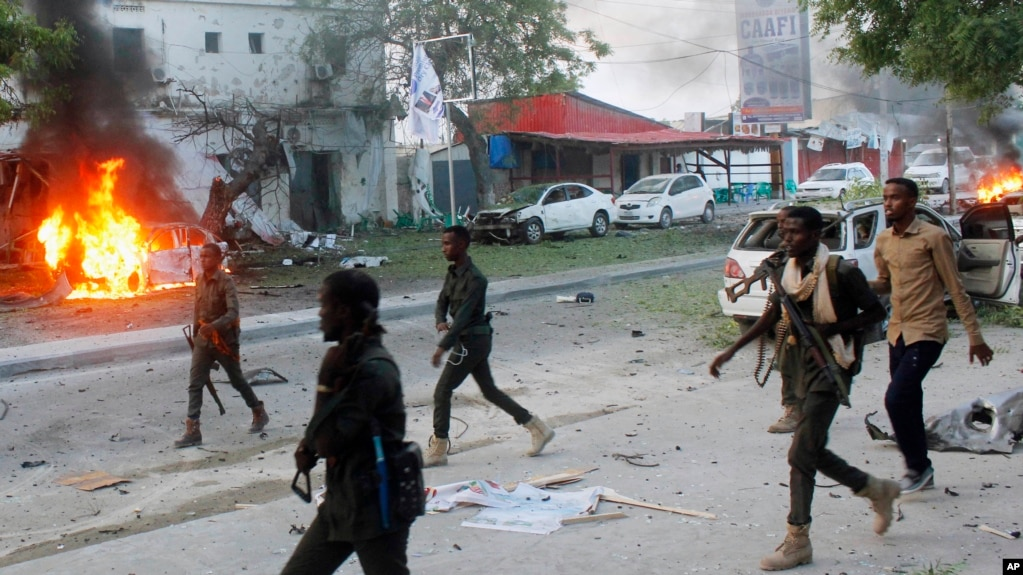 FILE - Security troops walk past burning cars after a fatal car bomb attack on a restaurant in Mogadishu, Somalia, May, 8, 2017. Al-Shabab militants claimed responsibility for the blast. Somalia's states on Sept. 8, 2018, suspended all ties with the central government, contending that it had taken its eye off the fight against al-Qaida-linked Islamist militants.