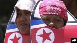 2012년 6월 2명의 필리핀 여성이 마닐라 북쪽 퀘존 시에서 북한의 미사일 발사에 항의하는 시위에 참가하고 있다. (자료사진)