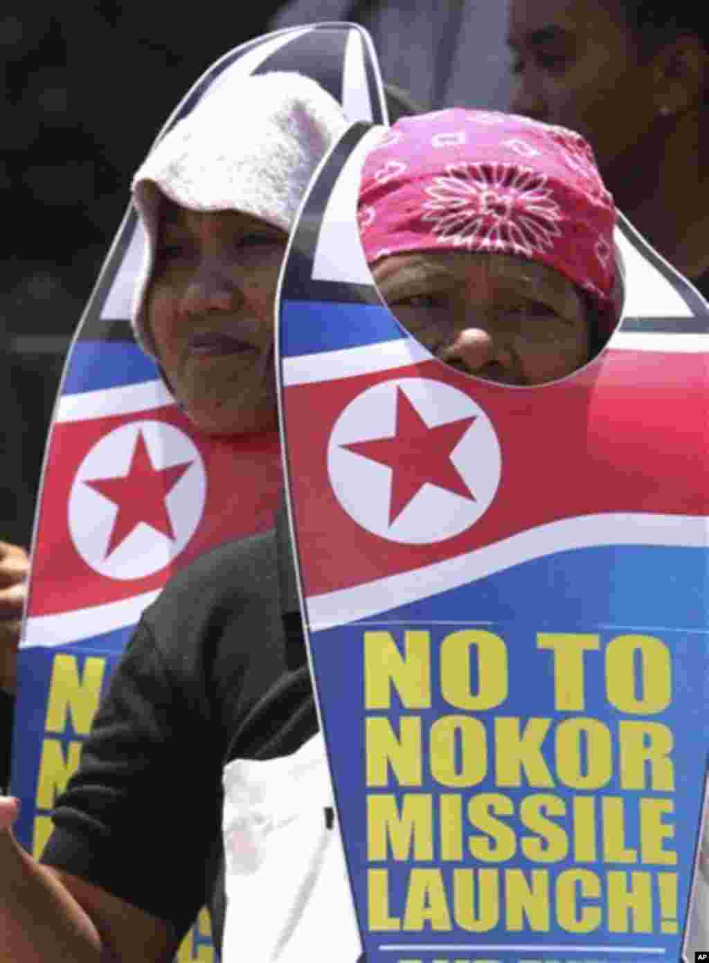 Two female protesters wearing a rocket shaped cut-out placards join a picket in protest of North Korea's rocket launch Friday, April 13, 2012 in suburban Quezon City, north of Manila, Philippines. The protesters demanded that North Korea stop any plans to