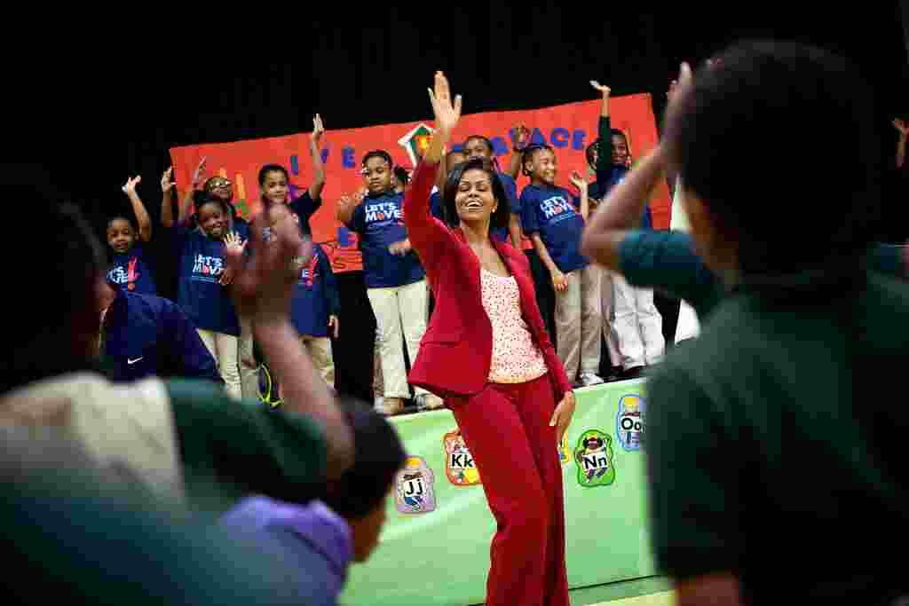 Michelle Obama hace ejercicio con estudiantes y atletas olímpicos en un evento del programa 'Let's Move!' en la escuela River Terrace en Washington, D.C., (21 de abril de 2010).