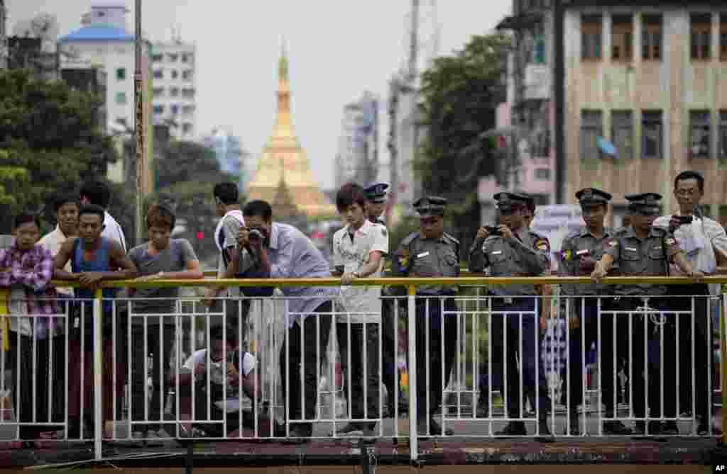 Cảnh sát Miến Điện và những người khác chụp ảnh của nhóm sinh viên ủng hộ dân chủ kỷ niệm 25 năm cuộc nổi dậy ngày 8 tháng 8 năm 1988 ở Rangoon, 8 tháng 8, 2013.
