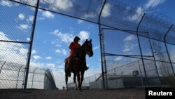FILE - An inmate rides a wild horse as part of the Wild Horse Inmate Program ( WHIP) at Florence State Prison in Florence, Arizona.