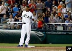 Congressman Cedric Richmond stands on third base after his triple in Congressional baseball game.