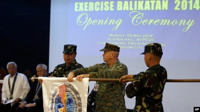 U.S. Marine Col. John Rutherford, 2nd from R, and Philippine Army Maj.Gen. Emeraldo Magnaye, 3rd from R, unfurl the joint U.S.-Philippines military exercise flag at Armed Forces of the Philippines headquarters in Manila, Philippines, on May 5, 2014.
