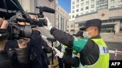一名警察擋住記者的鏡頭阻止拍攝審訊公民記者張展的上海浦東新區法院外景。 (2021年12月28日)
