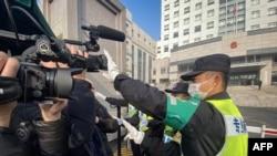 上海浦东新区法院外,一名警察阻止记者拍摄。(2021年12月28日)