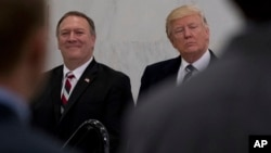 FILE - President Donald Trump, accompanied by then-CIA Director-designate Mike Pompeo, left, waits to speak at the Central Intelligence Agency in Langley, Virginia, Jan. 21, 2017.