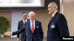 The United Nations Special Envoy for Syria, Staffan de Mistura (C) welcomes Bashar al-Jaafari, Syrian U.N. Ambassador, prior to a round of negotiations during the Intra Syria talks, at the European headquarters of the United Nations in Geneva, Switzerland