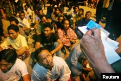 FILE - Indonesian migrant workers wait for Malaysian immigration officers to check their immigration status outside Kuala Lumpur.