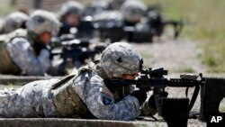 Female soldiers from 1st Brigade Combat Team, 101st Airborne Division train on a firing range while testing new body armor in Fort Campbell, Kentucky, Sept. 18, 2012.