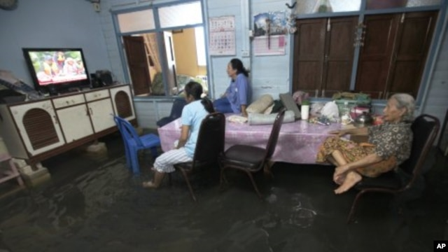Family members watch TV lifted to avoid flooding at their home in Bangkok, Thailand, October 3, 2011.