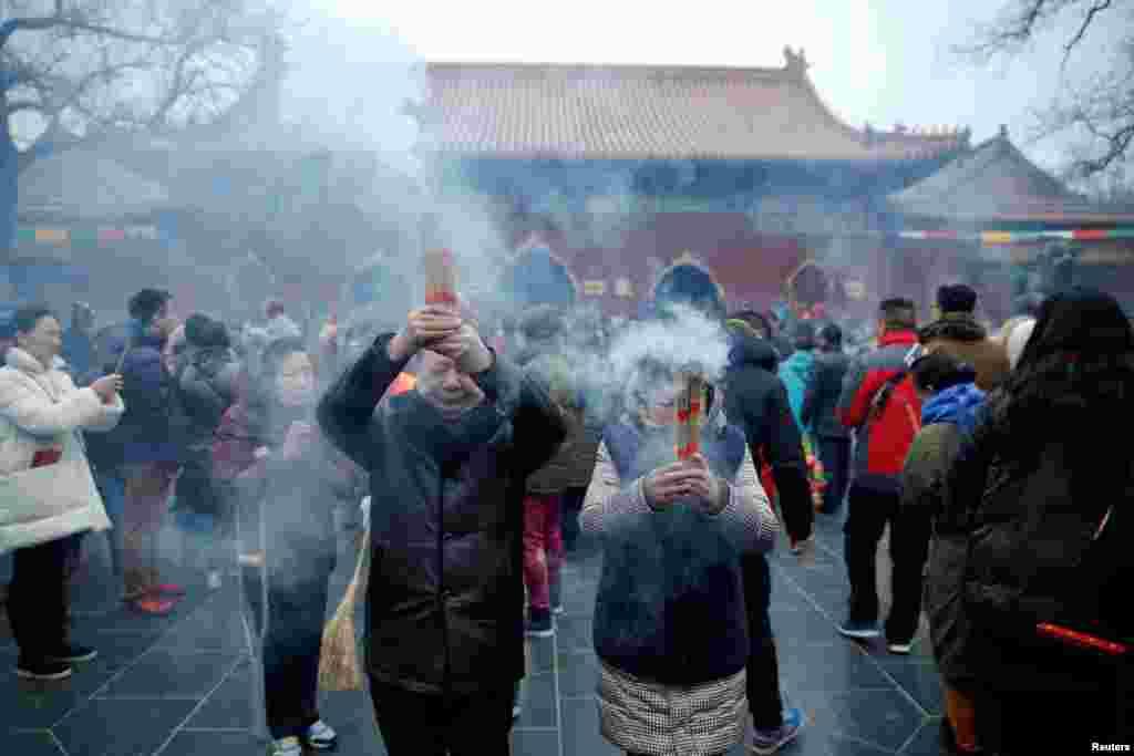 Warga membakar dupa dan berdoa untuk keberuntungan di Kuil Yonghegong Lama pada hari pertama tahun baru ayam jantan di Beijing (28/1). (Reuters/Damir Sagolj).