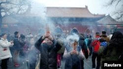 People burn incense sticks and pray for good fortune at Yonghegong Lama Temple on the first day of the lunar new year of the rooster in Beijing, China, Jan. 28, 2017.