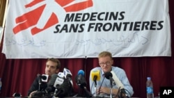 The general director of medical charity, Medecins Sans Frontieres (MSF), Christopher Stokes, right, talks as MSF's Country Representative for Afghanistan, Guilhem Molinie, left, listens, during a press conference at their office, in Kabul, Afghanistan, Oct. 8, 2015.