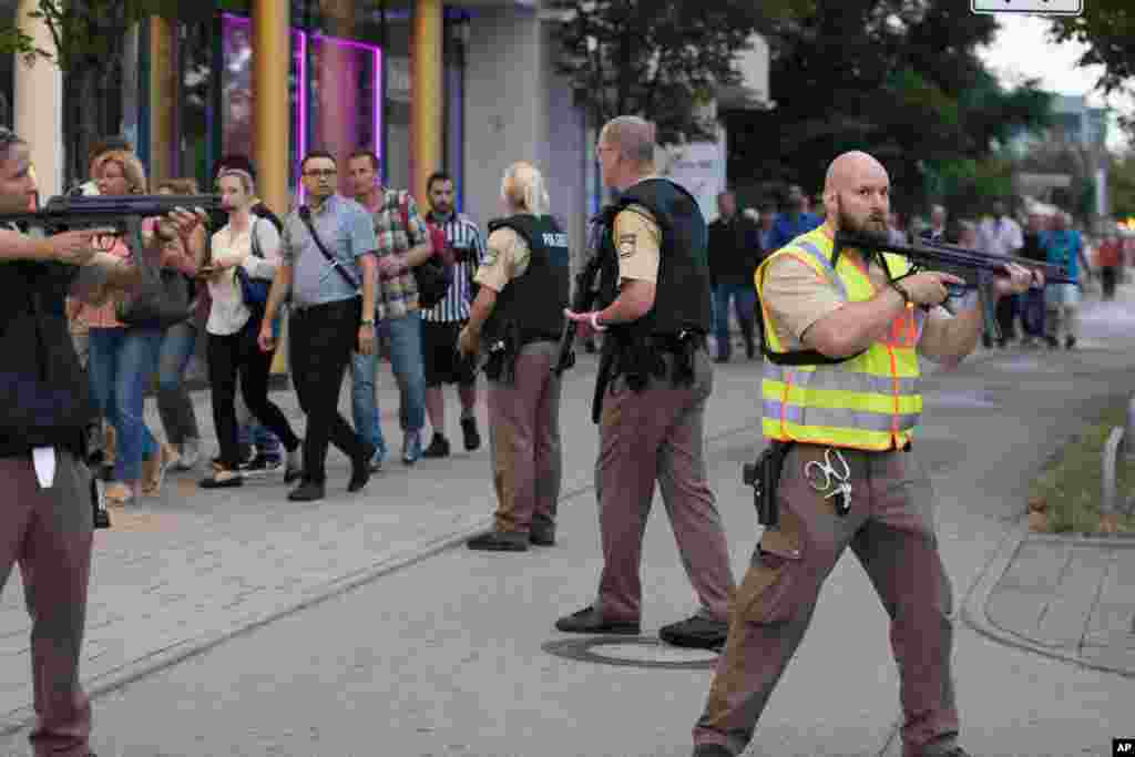 Police escort people who leave the Olympia mall in Munich, southern Germany, July 22, 2016 after shots were fired.