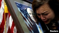 """Công dân Mỹ gốc Việt Mai Tran khóc bên bức ảnh của TNS John McCain sau khi tới khi sổ tang tại Đại sứ quán Mỹ ở Hà Nội hôm 27/8. Chính phủ Việt Nam """"trân trọng"""" những nỗ lực của TNS McCain trong việc hàn gắn quan hệ Việt-Mỹ."""