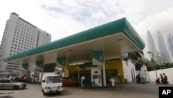 Motorists fill up their vehicles at Petronas petrol station in Kuala Lumpur, Malaysia, in this 2010 file photo. Many asian nations are seeing gains from lower oil prices. (AP Photo/Lai Seng Sin)
