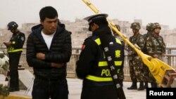 在中国新疆维吾尔自治区喀什的一条街上,警察检查一名男子的身份证,旁边有安全人员(2017年3月24日)