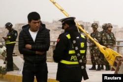在中國新疆維吾爾自治區喀什的一條街上,警察檢查一名男子的身份證,旁邊有安全人員(2017年3月24日)