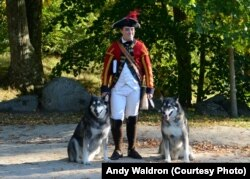 A citizen volunteer, dressed as an 18th century British soldier, poses for a picture with a couple of canine visitors at Minute Man National Historical Park in Concord, Massachusetts.