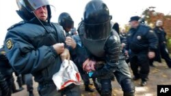 FILE - Riot police detain an anti-gay protester during an authorized gay rights rally in St. Petersburg, Russia, Oct. 12, 2013