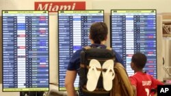 Passengers check the departure board at Miami International Airport, Sept. 7, 2017.