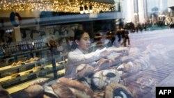 """Seorang pramuniaga di toko roti """"Chez Blandine"""", milik miliarder China Hu Keqin, di Beijing, 30 Januari 2018. Hu Keqin membeli lahan gandum di Indre dan Allier karena tertarik dengan gandum Perancis."""