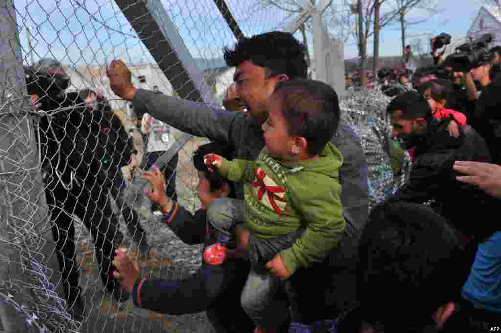 A man from Afghanistan carrying a baby cries as he pushes against the fence at the Greece-Macedonia border during a demonstration near the village of Idomeni, northern Greece, against Macedonia's refusal to allow Afghans to pass the border. Greece said that it was taking action to persuade Macedonia to take in Afghan migrants as thousands remained stranded at the border and the main port in Athens.