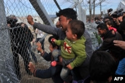A man from Afghanistan carrying a baby cries as he pushes against the fence at the Greece-Macedonia border during a demonstration near the village of Idomeni, northern Greece, on February 22, 2016.