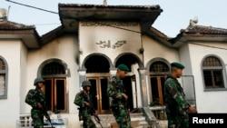 Tentara berjalan melintas sebuah masjid milik pengikut Ahmadiyah yang dibakar massa di Desa Ciampea, Jawa Barat, 2 Oktober 2010.