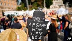 """A woman holds a banner reading """"Afghan sisters, you're not alone"""" during a demonstration in favor of Afghan women's rights, staged by women rights activists, in Rome, Sept. 25, 2021."""