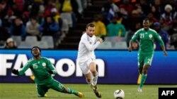 Dimitris Salpingidis của đội tuyển Hy Lạp (áo trắng) đi bóng qua Lukman Haruna (trái) và Nigeria Elderson Echiejile (phải) của Nigeria trong trận đấu tại Sân vận động Free State Stadium ở Bloemfontein, Nam Phi, ngày 17 Tháng 6, 2010