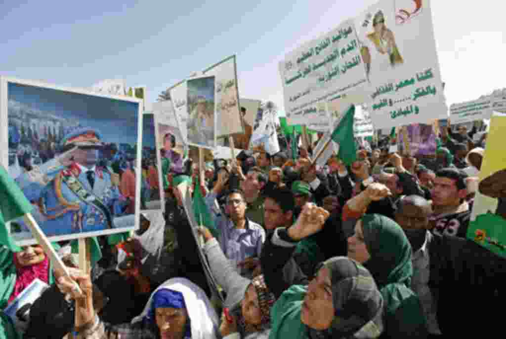 Pro-government supporters hold posters of Libyan leader Muammar Gaddafi as they chant slogans during a demonstration in Tripoli to counteract online calls for an anti-government 'day of rage,' February 17, 2011